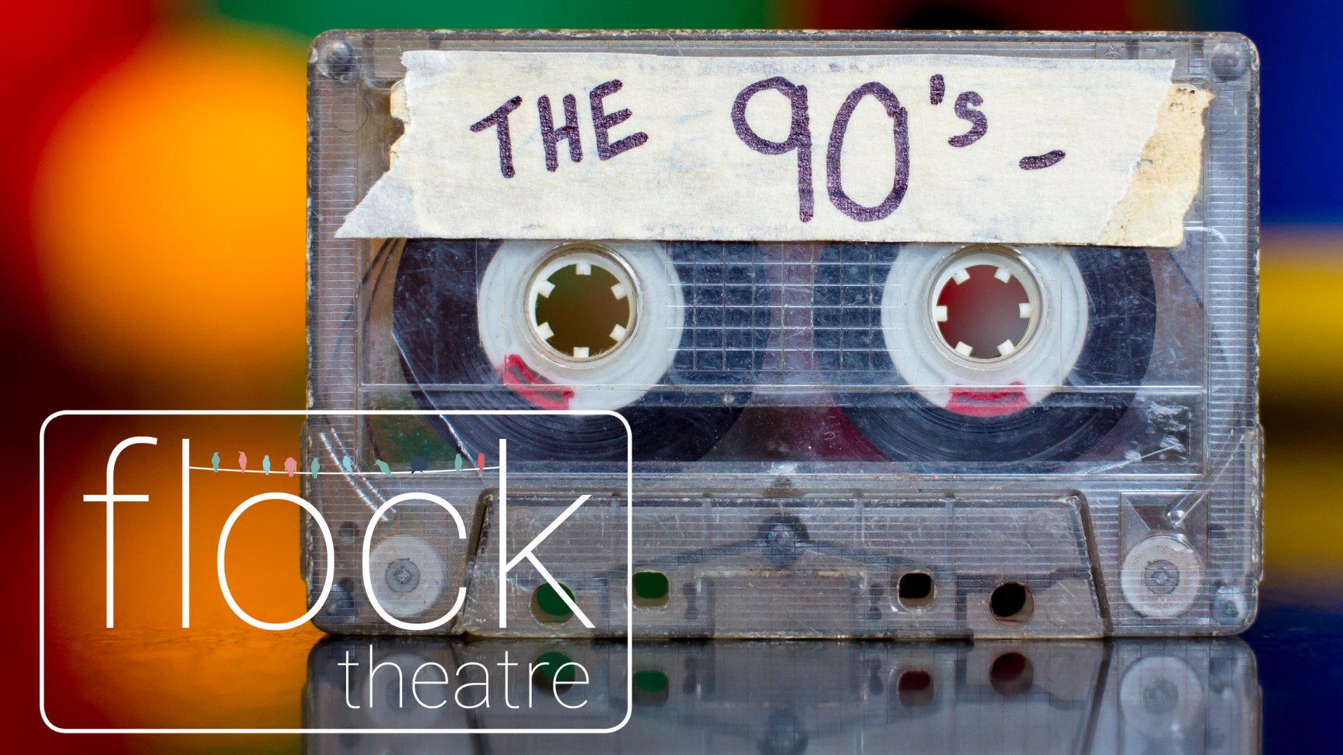 A cassette tape with a white sticker where it's written The 90s on a colorful background and the Flock logo.
